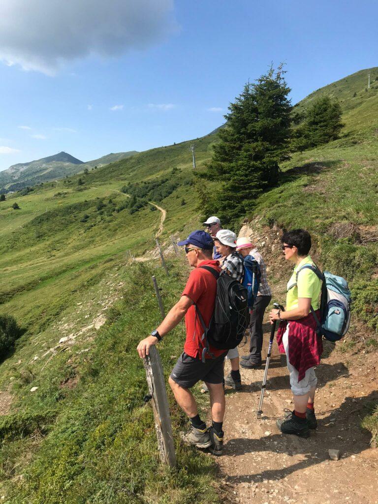 Die Wandergruppe geniesst die herrliche Aussicht Richtung Lenzerheide und Parpaner Rothorn.